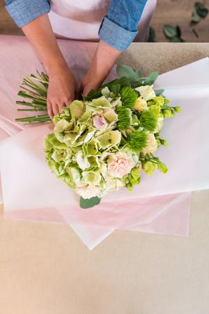 florist arranging beautiful flowers in craft paper