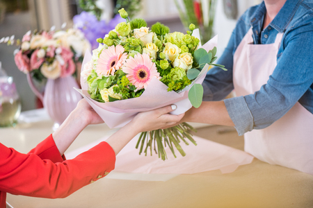 florist giving beautiful flower bouquet to client