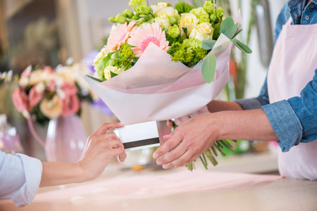 client giving credit card to florist holding bouquet