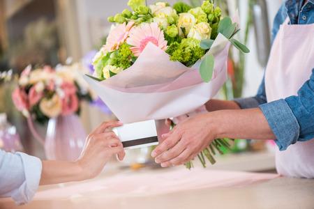 klant die creditcard geeft aan bloemist die boeket houdt