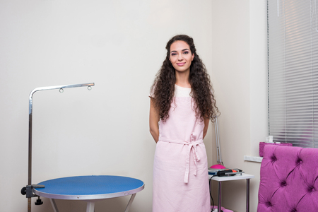 young groomer in apron smiling at camera in pet salon