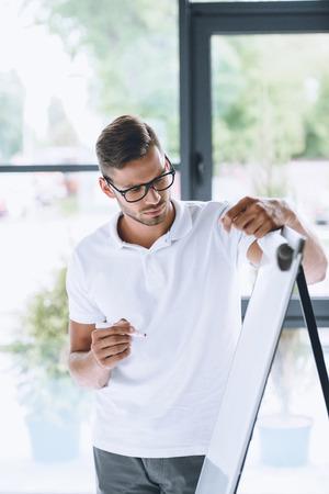 focused businessman making presentation at white board in office Banco de Imagens