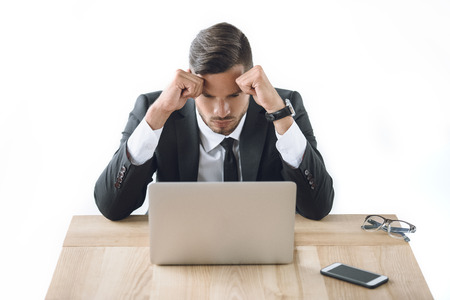 portrait of tired businessman sitting at workplace with laptop and smartphone