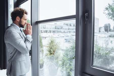 caucasian businessman standing at window in office and praying