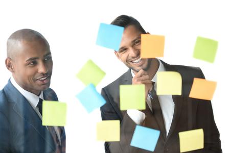 multicultural smiling businessmen looking at sticky notes Banco de Imagens