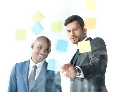 businessman pointing at sticky notes while discussing work with colleague