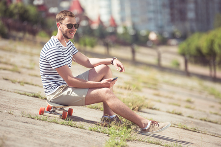 skateboarder: happy handsome man in sunglasses listening music on smartphone while sitting on skateboard in city Stock Photo