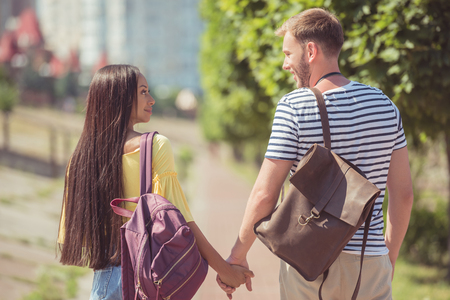 back view of young happy multiethnic couple with backpacks holding hands and walking in park