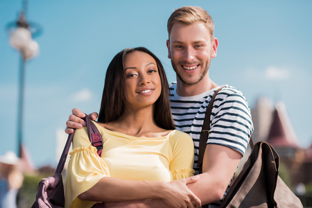 happy multiethnic couple with backpacks embracing and looking at camera