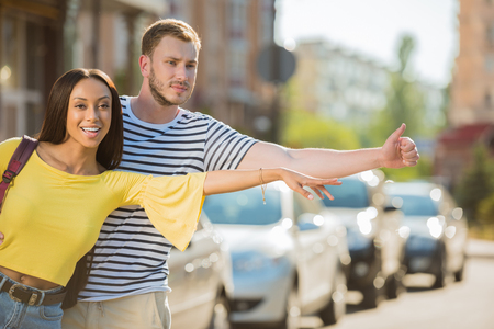 multiethnic couple of tourists hailing taxi in city