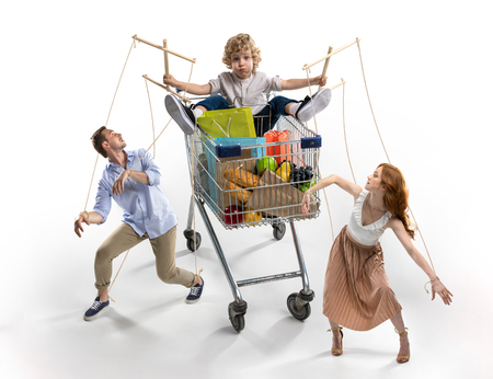 parents manipulated by little son in shopping cart isolated on white Stock Photo