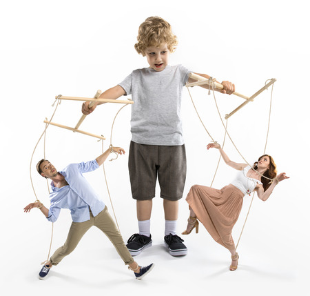 boy puppeteer controlling parents with strings isolated on white