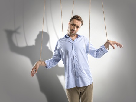 sad man on manipulating ropes with shadow of puppeteer behind isolated on grey