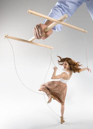 bijgesneden opname van hand van poppenspeler manipuleren vrouw