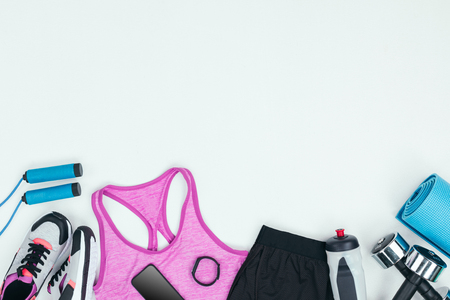 Sportswear with sneakers, smartphone, fitness tracker and fitness equipment