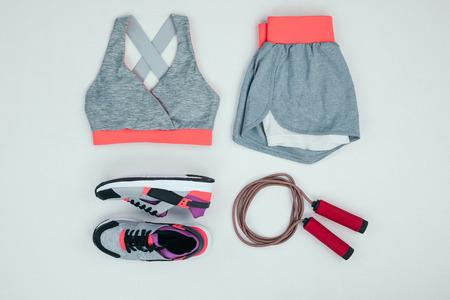 Ropa deportiva con zapatillas y cuerda de saltar aislado en gris Foto de archivo - 84966030