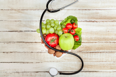 top view of stethoscope,various organic vegetables and fruits on wooden surface