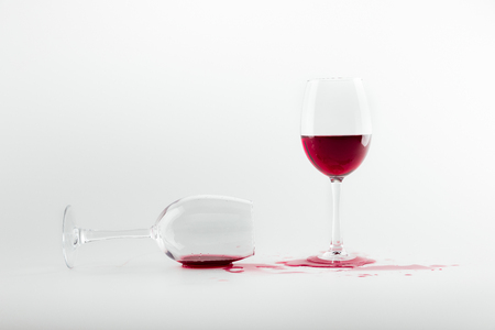 red wine in glasses and spilled out isolated on white