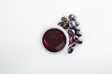 red wine in grass and ripe grapes isolated on white Stock Photo