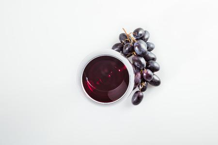 rode wijn in gras en rijpe druiven geïsoleerd op wit