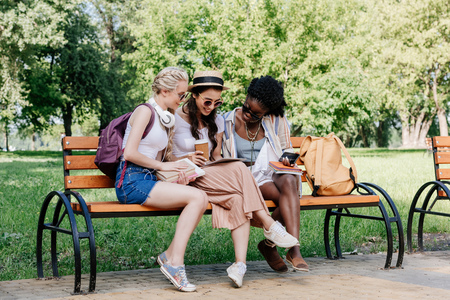beautiful women using tablet while resting on bench in park