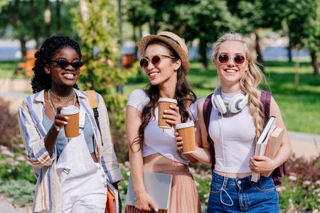 multicultural women with disposable cups of coffee in hands walking in park