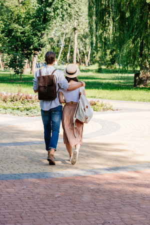 stylish couple walking in summer park together
