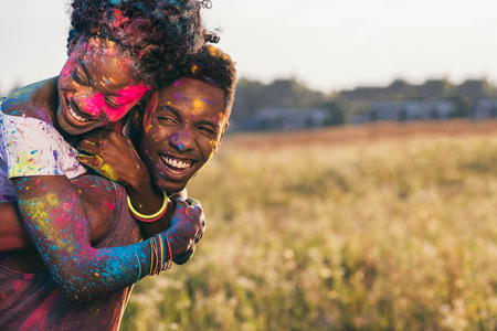 happy african american couple piggybacking at holi festival