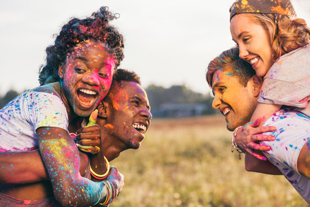 multiethnic couples piggybacking together at holi festival Stok Fotoğraf - 84972067