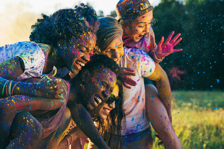 happy friends piggybacking together at holi festival