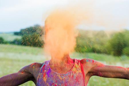african american man throwing powder during holi festival