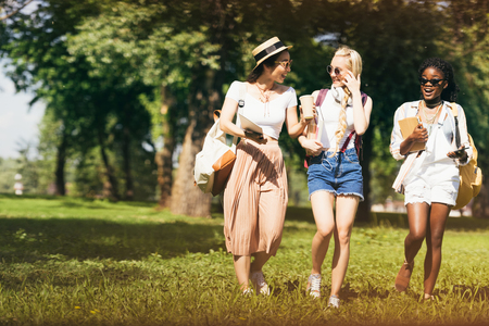 aantrekkelijke multi-etnische meisjes in zonnebril schoolboeken te houden tijdens het wandelen in het park