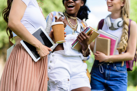 young multiethnic women holding books and digital tablet while talking in park Stock Photo - 84991999