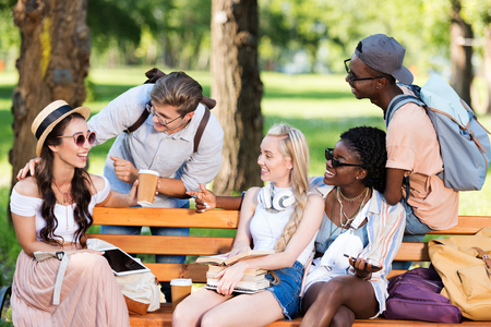 multiethnic students holding books and digital devices while interacting in park