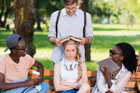electronic book: multiethnic group of students sitting together on bench in park