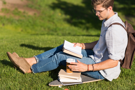 young man in spectacles reading book and drinking coffee while sitting on skateboard in park Фото со стока