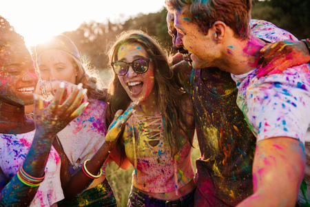 young multiethnic friends with colorful paint on clothes and bodies having fun together at holi festival