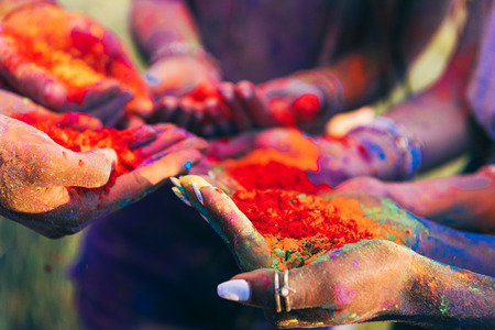 cloyoung people holding colorful paint in palms at holi festival