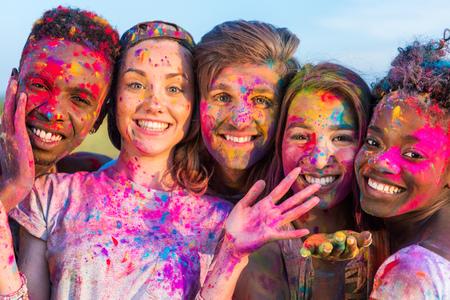 젊은 다민족적인 친구가 색상의 holi 축제 다채로운 가루로 재미