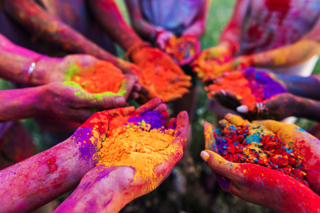 young people holding colorful powder in hands at holi festival