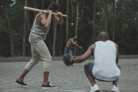 young multiethnic men playing baseball on court