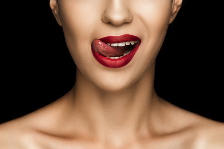 bijgesneden weergave van mooie vrouw likken lippen met rode lippenstift