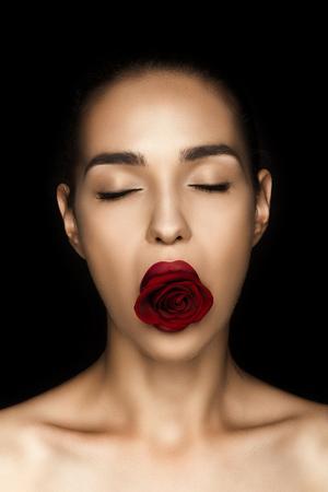Attraente donna nuda con gli occhi chiusi che tiene rosa rossa in labbra Archivio Fotografico - 85002398
