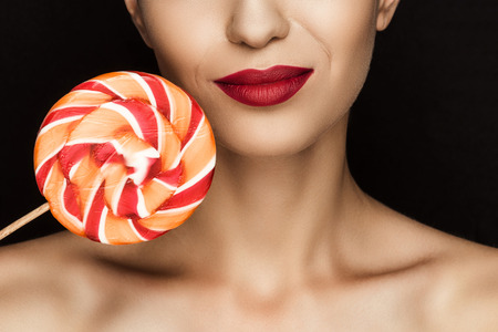 cropped view of beautiful naked woman with red lips holding lollipop Imagens
