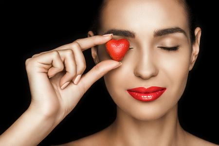 aantrekkelijke vrouw met gesloten ogen die rood hart gevormd suikergoed houden Stockfoto