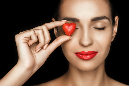 attractive woman with closed eyes holding red heart shaped candy Imagens