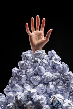 しわくちゃの紙の山から手を差し伸べる手のショットをトリミング