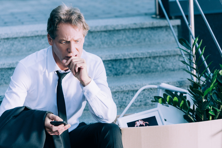 pensive mature businessman holding smartphone while sitting on stairs with cardboard box