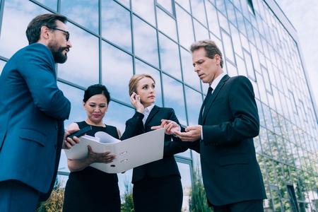 現代のオフィスビルの近くで、多民族ビジネスマンが論文を議論