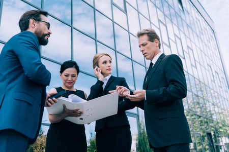 multiethnic businesspeople discussing papers near modern office building